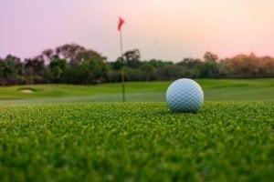 golf ball on putting green near hole